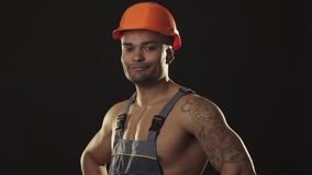 Happy muscular African male builder in hardhat smiling showing thumbs up stock photography