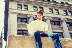 Young Handsome American Man traveling, working in New York. Wearing white shirt, blue pants, sitting on street outside vintage business office building Stock Images