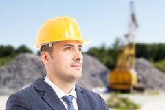 Young handsome architect on construction site. Young handsome architect wearing helmet and daydreaming as engineering industry concept on construction site royalty free stock photography