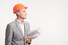 Young handsome architect engineer posing. Half-length portrait of young smiling handsome architect engineer in orange helmet posing with blueprints looking royalty free stock image