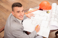 Young handsome architect engineer working on. Top view portrait of young smiling handsome architect engineer working on design plan sitting at the table with stock images