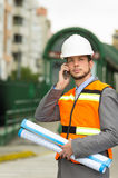 Young handsome architect supervising a. Construction using cell phone stock image