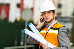 Young handsome architect supervising a. Construction using cell phone with buildings in the background Royalty Free Stock Photos