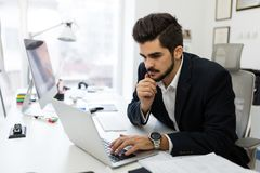 Young handsome architect working on laptop in office Royalty Free Stock Image