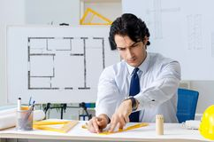 The young handsome architect working on the project. Young handsome architect working on the project stock photo