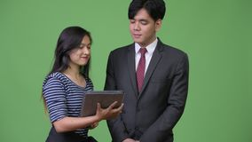 Young handsome Asian businessman and young Asian woman working together. Studio shot of young handsome Asian businessman and young beautiful Asian businesswoman stock video
