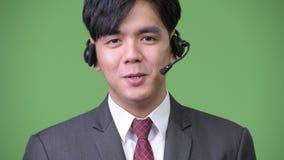 Young handsome Asian businessman working as call center representative