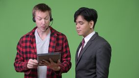Young handsome Asian businessman and young Scandinavian businessman working together. Studio shot of young Asian businessman and young Scandinavian businessman stock footage