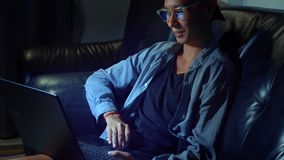 Young handsome Asian man in glasses with reflections using his laptop, sitting in the evening in the room. In the dark stock video footage