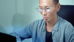 Young handsome asian man using his laptop, sitting at desk in office stock video