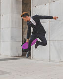 Young handsome Asian model jumping with his skateboard Stock Image