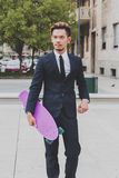 Young handsome Asian model posing with his skateboard Royalty Free Stock Photo