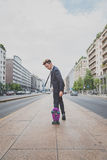 Young handsome Asian model posing with his skateboard Royalty Free Stock Photos