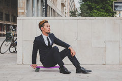Young handsome Asian model posing with his skateboard Stock Image