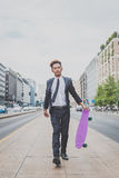 Young handsome Asian model walking with his skateboard Royalty Free Stock Photo
