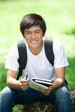 Young handsome Asian student with laptop stock image