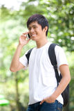 Young handsome Asian student talking on cell phone. And toothy smile in campus park Royalty Free Stock Images
