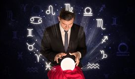 Astronaut looking for inspiration in his crystal magic ball. Young handsome astronaut looking for inspiration in his crystal magic ball royalty free stock image