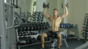 A young handsome athlete is actively engaged in sports exercises for the hands in the gym, training two hands with a. Dumbbell, gym, muscles, dumbbells, a stock video
