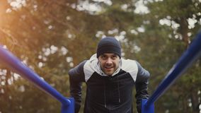 Young athlete man doing push-ups exercise on bars in winter park outdoors Royalty Free Stock Images