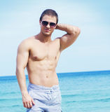Young, handsome and athletic man on a beach at summer Stock Photo