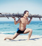 Young, handsome and athletic man training on the beach Stock Photos