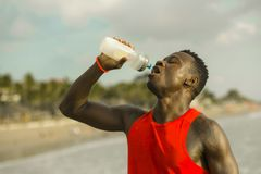 Young handsome and attractive black African American sport man tired and thirsty after running workout holding bottle drinking stock photography