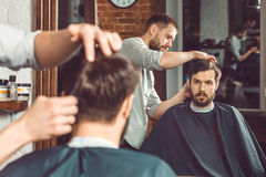 Young handsome barber making haircut of attractive man in barbershop Stock Images