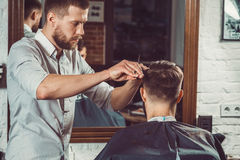 Young handsome barber making haircut of attractive man in barbershop Royalty Free Stock Image