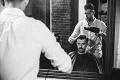 Young handsome barber making haircut for attractive man in barbershop royalty free stock photo