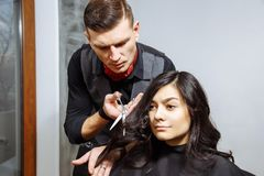 Young handsome barber making haircut of attractive woman in barbershop. royalty free stock photo
