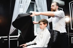Young handsome barber making haircut of boy in barbershop stock image