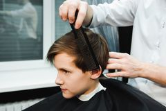 Young handsome barber making haircut of cute boy in barbershop royalty free stock photo