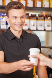 Young handsome barista giving coffee. Royalty Free Stock Photography