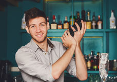 Young handsome barman in bar shaking and mixing alcohol cocktail. Young handsome barman in bar interior shaking and mixing alcohol cocktail. Professional stock photography