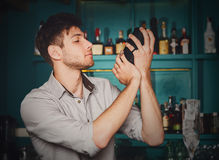 Young handsome barman in bar shaking and mixing alcohol cocktail. Young handsome barman in bar interior shaking and mixing alcohol cocktail. Professional royalty free stock photography
