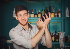 Young handsome barman in bar shaking and mixing alcohol cocktail. Young handsome barman in bar interior shaking and mixing alcohol cocktail. Professional stock images