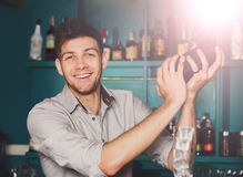 Young handsome barman in bar shaking and mixing alcohol cocktail. Young handsome barman in bar interior shaking and mixing alcohol cocktail. Professional royalty free stock photo