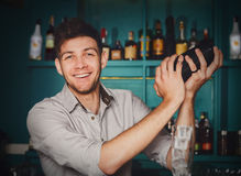 Young handsome barman in bar shaking and mixing alcohol cocktail. Young handsome barman in bar interior shaking and mixing alcohol cocktail. Professional stock image