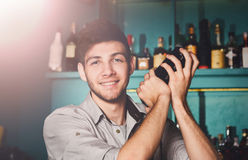 Young handsome barman in bar shaking and mixing alcohol cocktail. Young handsome barman in bar interior shaking and mixing alcohol cocktail. Professional royalty free stock photos