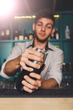 Young handsome barman in bar shaking and mixing alcohol cocktail. Young handsome barman in bar interior shaking and mixing alcohol cocktail. Professional royalty free stock images