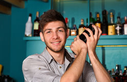 Young handsome barman in bar shaking and mixing alcohol cocktail. Young handsome barman in bar interior shaking and mixing alcohol cocktail. Professional royalty free stock image
