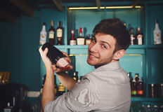 Young handsome barman in bar shaking and mixing alcohol cocktail. Young handsome smiling barman in bar interior shaking and mixing alcohol cocktail. Professional royalty free stock photos