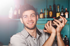 Young handsome barman in bar shaking and mixing alcohol cocktail. Young handsome smiling barman in bar interior shaking and mixing alcohol cocktail. Professional royalty free stock image