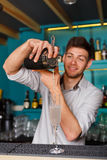 Young handsome barman pouring cocktail drink into glass Stock Images