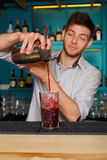 Young handsome barman pouring cocktail drink into glass. Young handsome barman in bar interior pouring red alcohol to cocktail drink from shaker. Professional stock photos