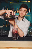 Young handsome barman pouring cocktail drink into glass. Young handsome barman in bar interior pouring red alcohol to cocktail drink from shaker. Professional royalty free stock images