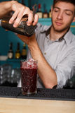 Young handsome barman pouring cocktail drink into glass. Young handsome barman in bar interior pouring red alcohol to cocktail drink from shaker. Professional royalty free stock photography