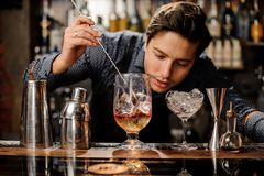 Young barman stirring fresh alcoholic cocktail with syrups. Young and handsome barman stirring fresh alcoholic cocktail with sweet fruit syrups on the bar stock photography
