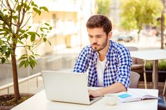 Young handsome bearded brunet is browsing on his laptop, sitting. Outdoors on a summer day, with note pad and cup of coffee, nice city view behind stock photos